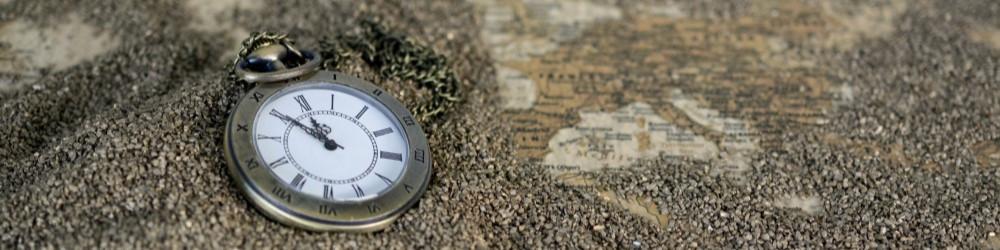 Klok in zand op een wereldkaart